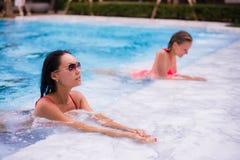 Mujeres jovenes que se relajan en la piscina Imagen de archivo libre de regalías