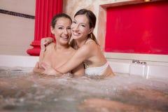 Mujeres jovenes que se relajan en la tina caliente Imagenes de archivo