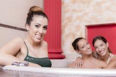 Mujeres jovenes que se relajan en la tina caliente Fotografía de archivo libre de regalías