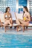 Mujeres jovenes que se relajan por la piscina Fotografía de archivo libre de regalías
