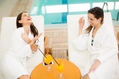 Mujeres jovenes que se relajan por la piscina Fotografía de archivo