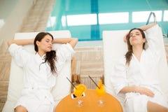 Mujeres jovenes que se relajan por la piscina Foto de archivo libre de regalías