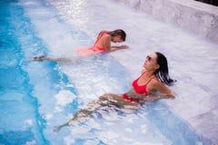 Mujeres jovenes que se relajan por la piscina Imagenes de archivo