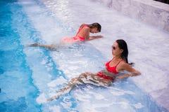 Mujeres jovenes que se relajan por la piscina Fotos de archivo