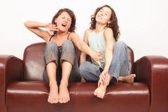 Mujeres jovenes que se sientan en el acabamiento del sofá que ve la TV Fotos de archivo