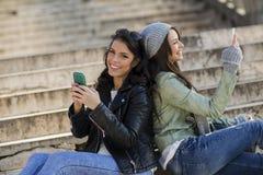 Mujeres jovenes que se sientan en las escaleras con los teléfonos móviles Imágenes de archivo libres de regalías