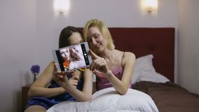Mujeres jovenes que son selfies de fabricación tontos en la tableta metrajes