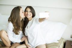 Mujeres jovenes que toman el selfie en la cama Foto de archivo