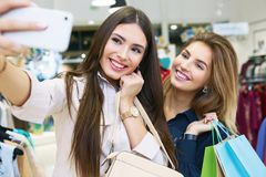Mujeres jovenes que toman el selfie mientras que hacia fuera en un día de compras Fotos de archivo