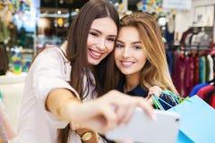 Mujeres jovenes que toman el selfie mientras que hacia fuera en un día de compras Imágenes de archivo libres de regalías