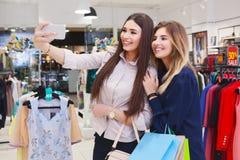 Mujeres jovenes que toman el selfie mientras que hacia fuera en un día de compras Imagen de archivo libre de regalías