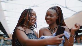 Mujeres jovenes que toman el selfie por el teléfono móvil en alameda almacen de metraje de vídeo