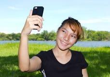Mujeres jovenes que toman imágenes de ellos mismos con un teléfono móvil Foto de archivo libre de regalías