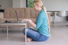 Mujeres jovenes que usan el ordenador portátil en el piso Imágenes de archivo libres de regalías