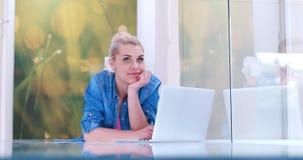 Mujeres jovenes que usan el ordenador portátil en el piso Fotografía de archivo