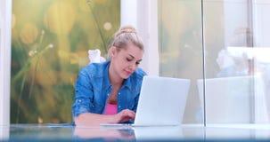 Mujeres jovenes que usan el ordenador portátil en el piso Foto de archivo libre de regalías