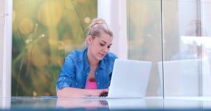 Mujeres jovenes que usan el ordenador portátil en el piso Imagen de archivo libre de regalías