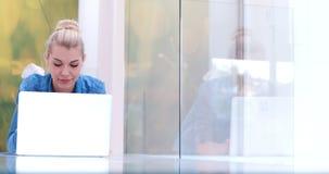 Mujeres jovenes que usan el ordenador portátil en el piso Foto de archivo