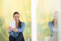 Mujeres jovenes que usan la tableta en el piso Imágenes de archivo libres de regalías