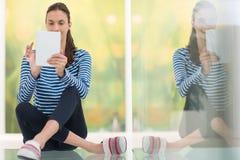 Mujeres jovenes que usan la tableta en el piso Fotos de archivo libres de regalías