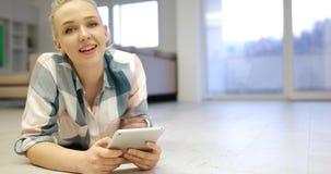 Mujeres jovenes que usan la tableta en el piso Imagen de archivo