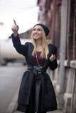 Mujeres jovenes rubias de moda que caminan en la calle - señalar el finger en algo Imagen de archivo libre de regalías