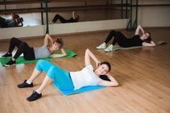 Mujeres jovenes sanas que hacen ejercicio en las esteras para la aptitud en el gimnasio imagenes de archivo