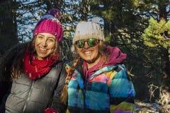 Mujeres jovenes sonrientes bajo caída del vsnow que lleva la ropa caliente adentro Imagen de archivo libre de regalías