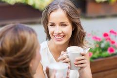 Mujeres jovenes sonrientes con las tazas de café en el café Imagen de archivo libre de regalías