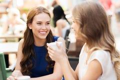 Mujeres jovenes sonrientes con las tazas de café en el café Foto de archivo libre de regalías