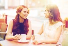 Mujeres jovenes sonrientes con las tazas de café en el café Imagen de archivo