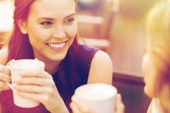 Mujeres jovenes sonrientes con las tazas de café en el café Fotografía de archivo libre de regalías