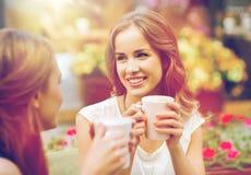 Mujeres jovenes sonrientes con las tazas de café en el café Imágenes de archivo libres de regalías