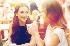 Mujeres jovenes sonrientes con las tazas de café en el café Imagenes de archivo
