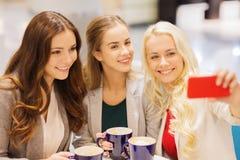 Mujeres jovenes sonrientes con las tazas y smartphone Imagen de archivo