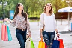 Mujeres jovenes sonrientes con los bolsos en compras Imagen de archivo libre de regalías