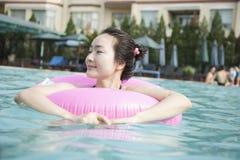 Mujeres jovenes sonrientes en la piscina con un tubo inflable, mirando lejos Fotografía de archivo