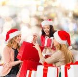 Mujeres jovenes sonrientes en los sombreros de santa con los regalos Fotografía de archivo