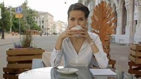 Mujeres jovenes sonrientes que beben el café o el té y que cotillean en el café al aire libre Fotografía de archivo libre de regalías