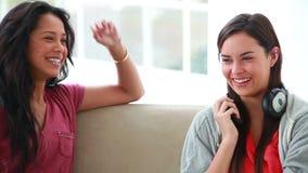 Mujeres jovenes sonrientes que hablan el uno al otro almacen de metraje de vídeo