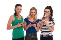 Mujeres jovenes sonrientes que mandan un SMS en sus teléfonos Imagen de archivo libre de regalías