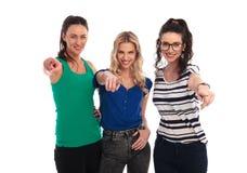 Mujeres jovenes sonrientes que señalan sus fingeres Fotos de archivo
