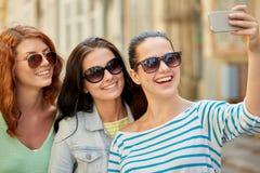 Mujeres jovenes sonrientes que toman el selfie con smartphone Imágenes de archivo libres de regalías