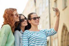 Mujeres jovenes sonrientes que toman el selfie con smartphone Fotos de archivo