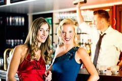 Mujeres jovenes y camarero en club o barra imagen de archivo libre de regalías