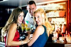 Mujeres jovenes y camarero en club o barra fotos de archivo