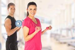 Pares jovenes que ejercitan con los pesos junto en el gimnasio imagen de archivo libre de regalías