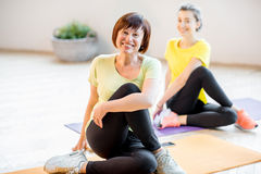 Mujeres jovenes y más viejas que hacen yoga fotografía de archivo libre de regalías