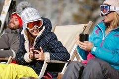 Mujeres junto que toman el sol y que beben en café en terreno del esquí Fotos de archivo libres de regalías