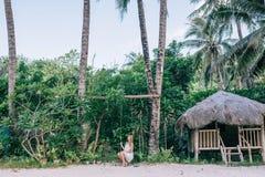 Mujeres largas hermosas del pelo en el vestido blanco que se sienta en el oscilación en el jardín tropical fotografía de archivo